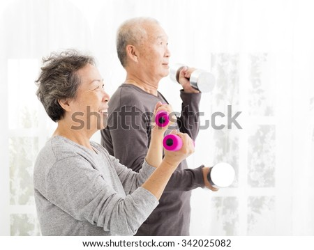happy senior couple exercising with dumbbells  - stock photo