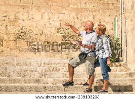Happy senior couple exploring old town of la Valletta with city map - Concept of active elderly and travel lifestyle without age limitation - Trip to european mediterranean wonders - stock photo