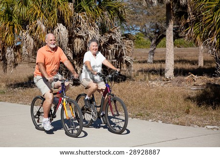 Happy senior couple gets in shape riding their bicycles. - stock photo