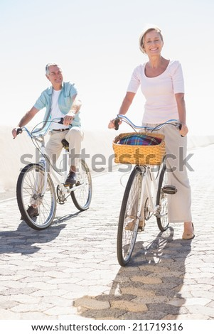 Happy senior couple going for a bike ride on a sunny day - stock photo