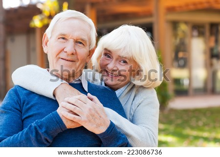 Happy senior couple. Happy senior couple bonding to each other and smiling while standing outdoors and in front of their house  - stock photo