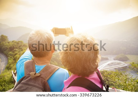 happy Senior couple hiking on mountains and taking selfies - stock photo