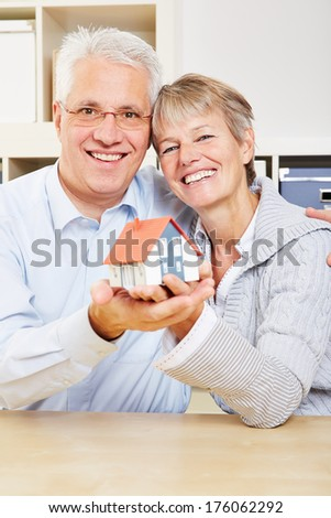 Happy senior couple holding a small house in their hands - stock photo