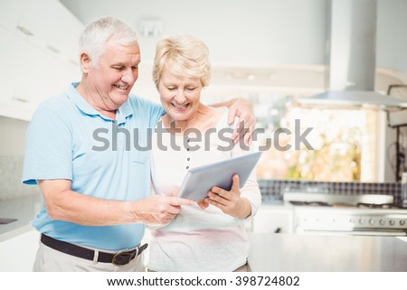 Happy senior couple holding digital tablet at home - stock photo