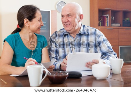 Happy senior couple holding financial documents - stock photo