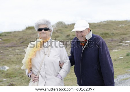 Happy senior couple holding hands and smiling - stock photo