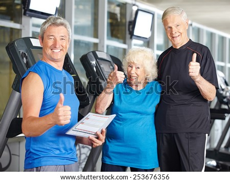 Happy senior couple in gym holding thumbs up with fitness trainer - stock photo