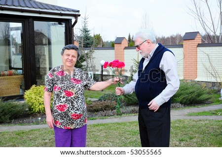 Happy senior couple in love giving flower, outdoors