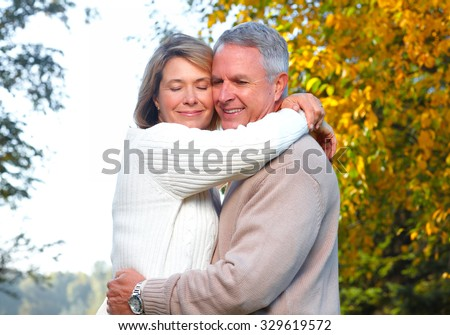 Happy senior couple in park. Autumn and fall background. - stock photo