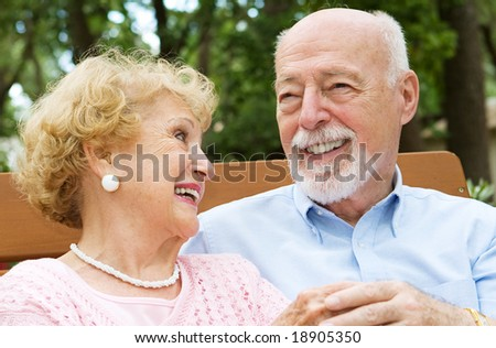 Happy senior couple laughing together.  She is wearing a hearing aid. - stock photo