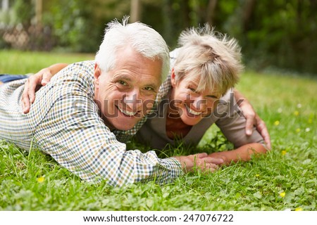 Happy senior couple laying on a meadow in summer - stock photo