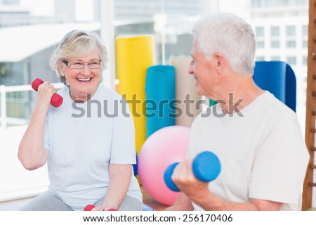Happy senior couple lifting dumbbells in gym - stock photo