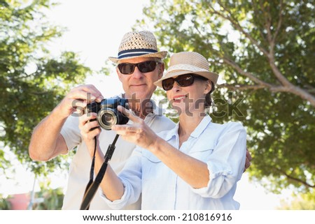 Happy senior couple looking at their camera on a sunny day - stock photo