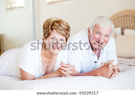 happy senior couple lying on bed - stock photo