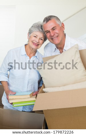 Happy senior couple moving into new home smiling at camera - stock photo