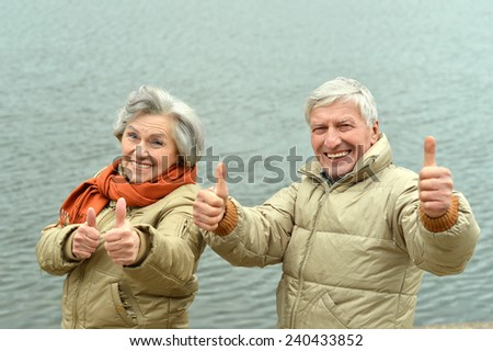 Happy senior couple near lake - stock photo