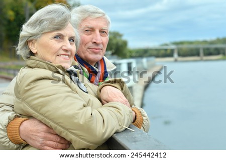 Happy senior couple near lake - stock photo
