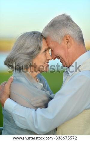 Happy senior couple  near lake during sunset at summer - stock photo