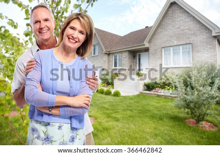 Happy senior couple near new house. - stock photo