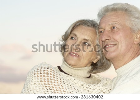 Happy senior couple on a sky background