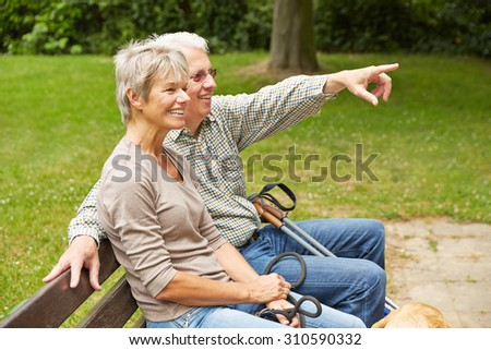Happy senior couple on park bench pointing with finger into the distance - stock photo