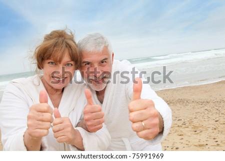 Happy senior couple on spa resort beach - stock photo