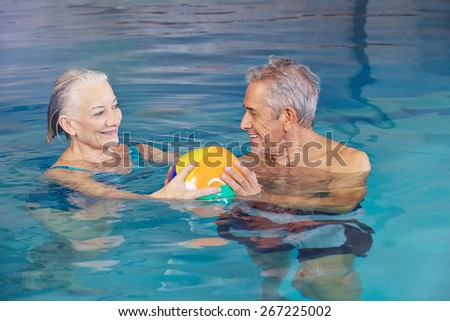 Happy senior couple playing water ball with beach ball in swimming pool - stock photo