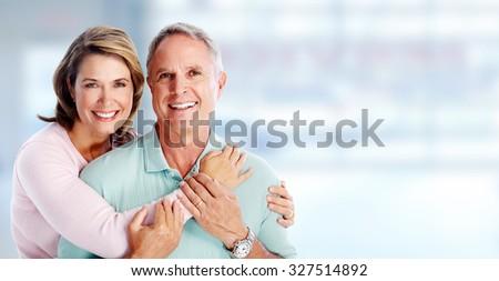 Happy senior couple portrait over blue background. - stock photo