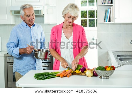 Happy senior couple preparing vegetables in kitchen - stock photo