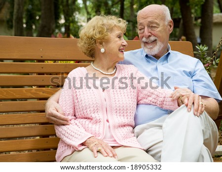 Happy senior couple relaxes together on a park bench. - stock photo