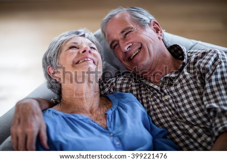 Happy senior couple relaxing on sofa and smiling at home - stock photo