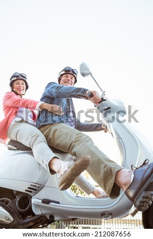 Happy senior couple riding a moped on a sunny day - stock photo