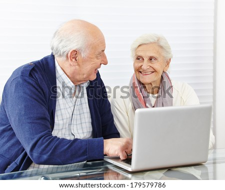 Happy senior couple shopping in internet with laptop computer - stock photo