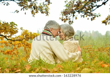 Happy senior couple sitting in autumn park