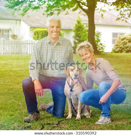 Happy senior couple sitting in garden with labrador retriever dog - stock photo