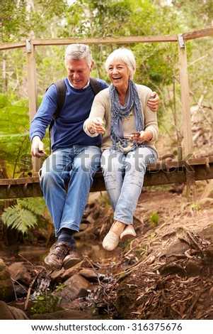 Happy senior couple sitting on a bridge in forest, vertical - stock photo