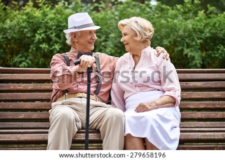 Happy senior couple sitting on bench in park and talking - stock photo