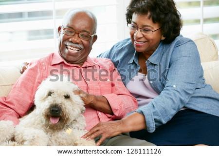 Happy Senior Couple Sitting On Sofa With Dog - stock photo