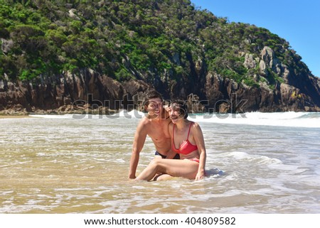 Happy senior couple sitting on the beach after swimming, having fun, laughing, smiling with toothy smile, in love with each other. Senior people travel the world on retirement. Australia - stock photo