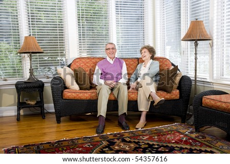 Happy senior couple sitting together on living room couch - stock photo