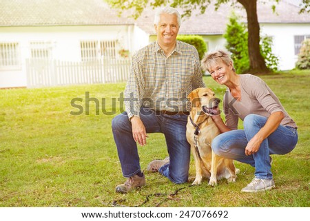 Happy senior couple sitting with house and labrador retriever in a garden - stock photo