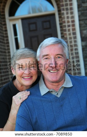 Happy Senior Couple smiling outside in front of their house - stock photo