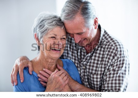 Happy senior couple smiling while embracing at home - stock photo