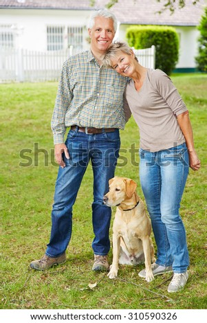 Happy senior couple standing with dog in front of their house - stock photo