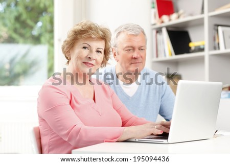 Happy senior couple surfing on internet. Planning for retirement at home.  - stock photo