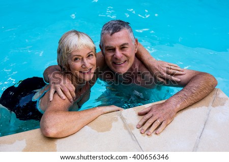 Happy senior couple swimming in pool - stock photo