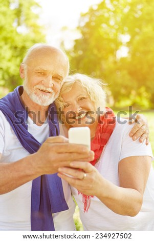 Happy senior couple taking a selfie with smartphone in a fall garden - stock photo