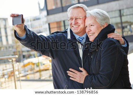 Happy senior couple taking pictures of themselves with a smartphone - stock photo