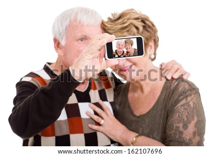 happy senior couple taking self portrait with smart phone isolated on white - stock photo