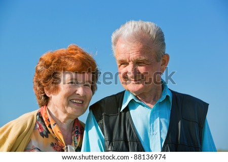 Happy senior couple together in love, outside, blue sky - stock photo